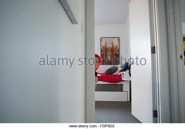 Curious boy peering from bedroom doorway - Stock Image