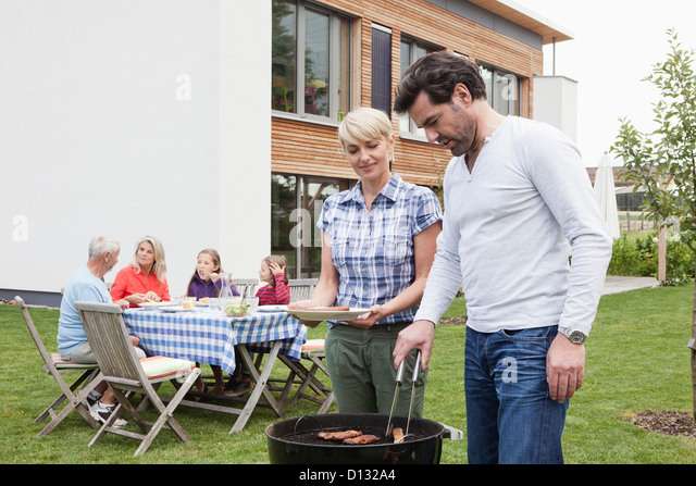 Germany, Bavaria, Nuremberg, Couple grilling barbecue, family sitting in background - Stock Image