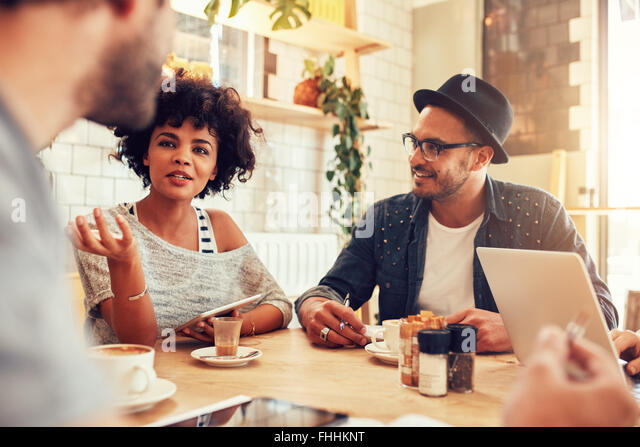 Portrait of young woman talking with friends at a cafe. Group of young people meeting at a coffee shop. - Stock Image