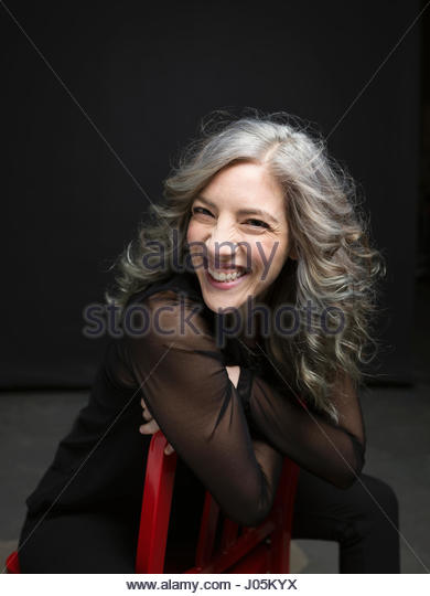 Portrait enthusiastic laughing woman with gray hair against black background - Stock Image