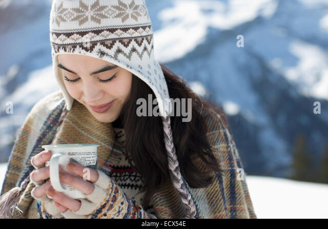 Smiling woman in knit hat drinking hot cocoa outdoors - Stock Image
