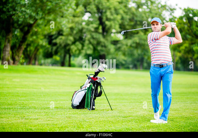 Golfer practicing and concentrating before and after shot during a nice sunny day - Stock Image