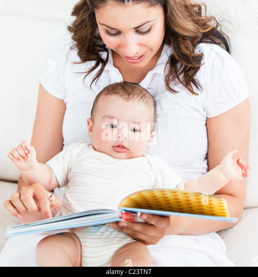 Bright mother showing images in a book to her cute little son - Stock Image