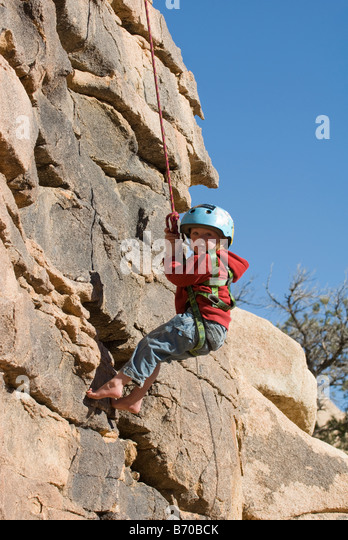 Boy rappelling cliff face, Joshua Tree National Park, California. - Stock Image