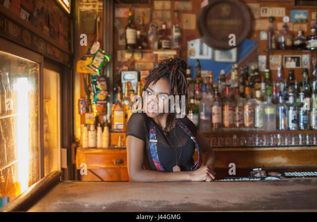 A young woman at a bar. - Stock Image