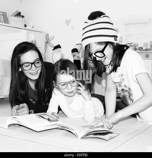 Girls (4-5), (10-11, 12-13) reading book - Stock Image