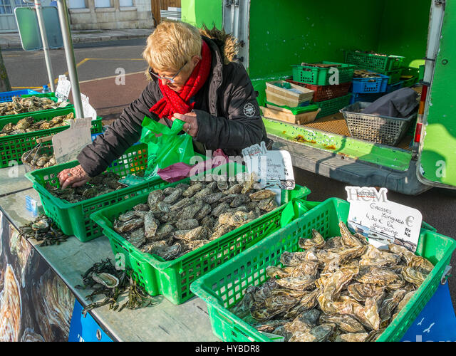 French Oyster seller with open-air market stall. - Stock Image