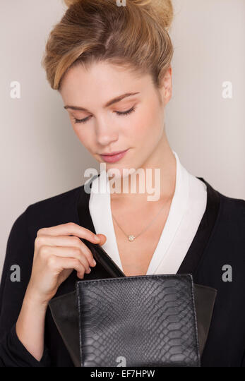 Beautiful woman checking her makeup bag - Stock Image