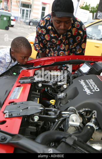 Florida Coconut Grove Grand Avenue Bahamas Goombay Festival Black father son new Chevrolet car automobile engine - Stock Image