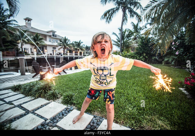 A young boy with sparklers wearing a cool dude t-shirt. - Stock Image