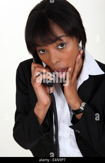 Shocked woman taking on the phone - Stock Image