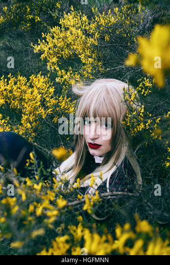 Portrait of a young woman between a lot of yellow flowers - Stock Image