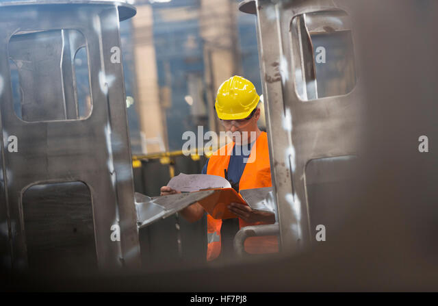 Steel worker reviewing paperwork in factory - Stock Image