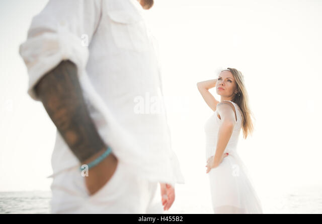 happy just married young wedding couple celebrating and have fun at beautiful beach sunset - Stock Image