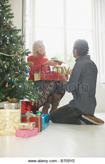 Couple exchanging Christmas gifts - Stock Image