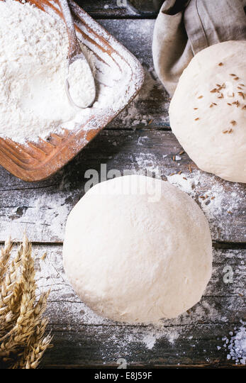 Baking bread. Dough on wooden table with flour, rolling-pin and jars with backing ingredients. Top view - Stock Image