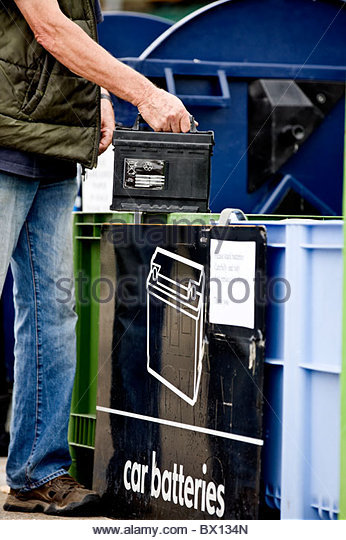 A senior man recycling a car battery, close-up - Stock Image