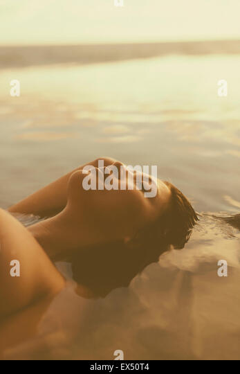 Young Woman Floating in Water - Stock Image