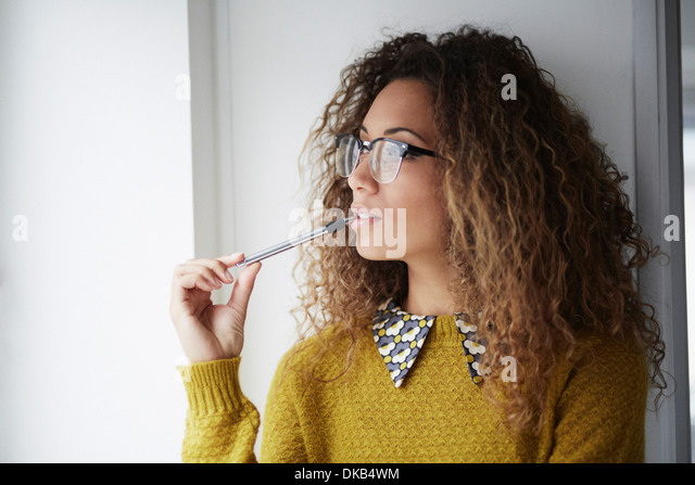 Female office worker holding pen - Stock Image