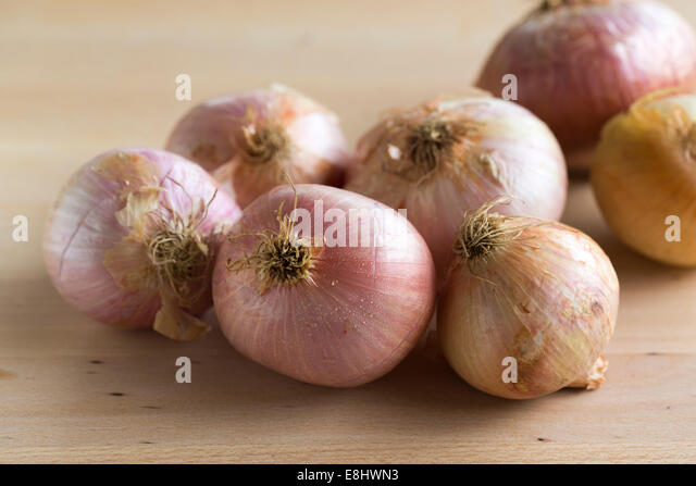 group of pink toned figuera Spanish onions on light wood table, - Stock Image