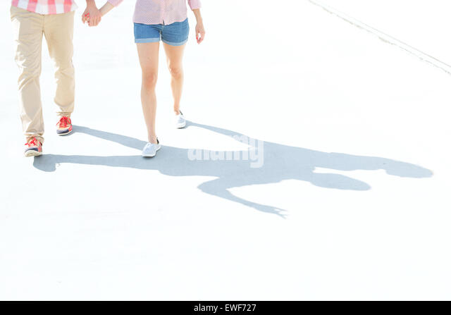 Low section of couple walking on street - Stock Image
