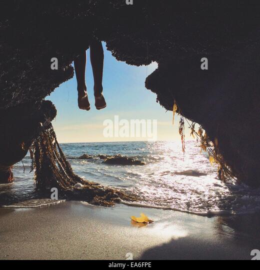 Person's legs hanging in front of cave entrance on beach - Stock Image