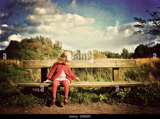 Little girl waiting on bench in countryside. - Stock-Bilder