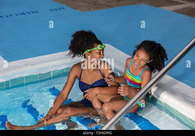 High angle view of girls sitting in swimming pool side by side laughing - Stock Image