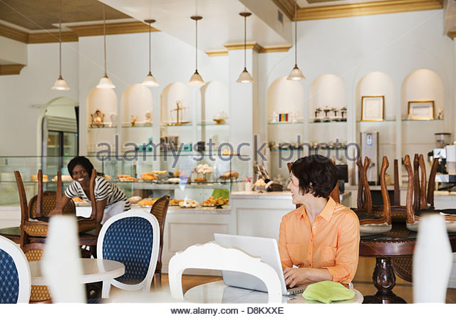 Female small business owner and employee working in coffee shop - Stock Image