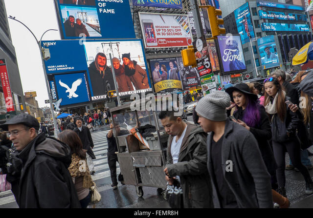 Tourists and advertising billboards, Times Square, New York, USA - Stock Image
