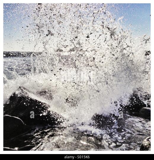 Sea crashing on rocks close up - Stock Image