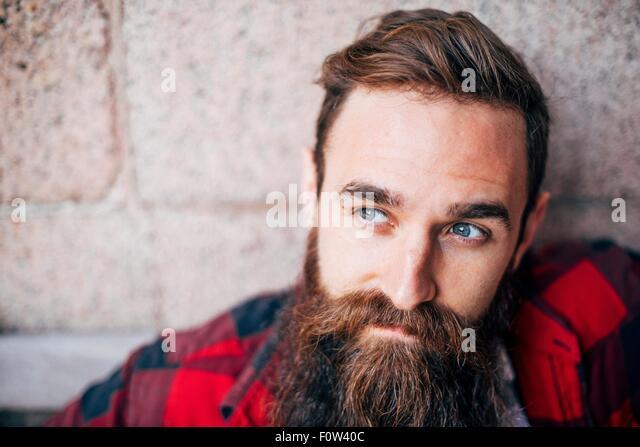Portrait of man with beard looking away - Stock-Bilder