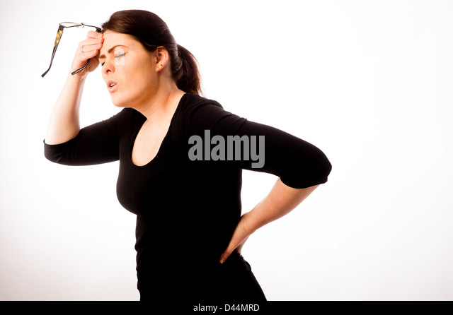 A young woman, brown hair, suffering back pain, tension stress  UK, - Stock Image