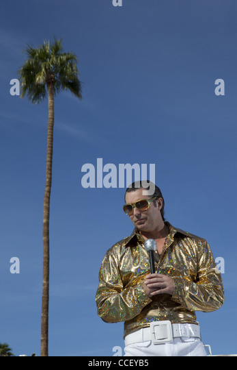 Low angle view of middle-aged man holding microphone - Stock Image
