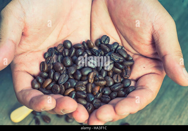 abstract blur coffee bean was selected on hand with vintage filter - can use to display or montage on product - Stock Image