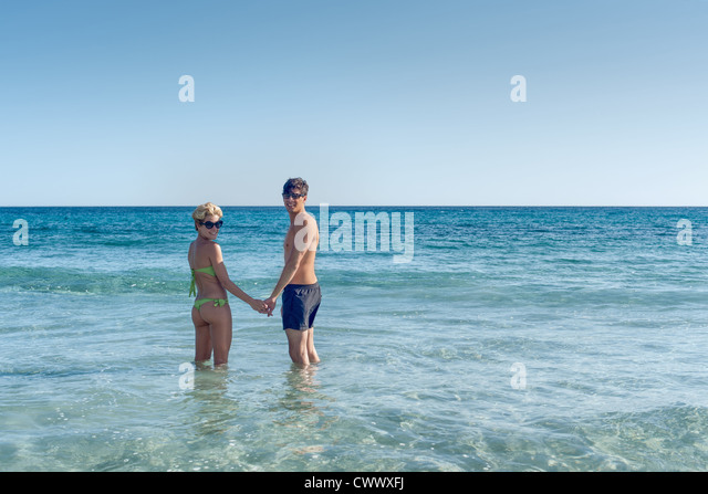 Couple standing in ocean together - Stock Image