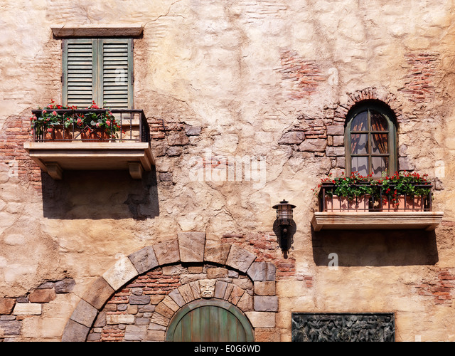 Wall of an old rustic house with flowers under windows, antique architecture in Venetian style - Stock Image
