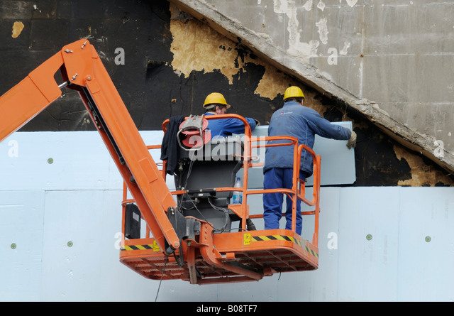 Two workers in a hydraulic lift, elevating platform aka cherry picker or boom lift mounting styrofoam insulation - Stock Image