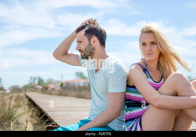 Portrait of young couple on beach looking sad - Stock Image