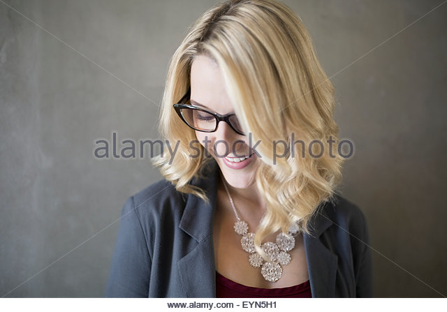 Portrait smiling blonde businesswoman with eyeglasses looking down - Stock Image