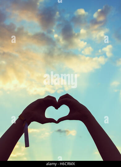 Silhouette of a hands making a heart shape with a beautiful sky as background - Stock Image
