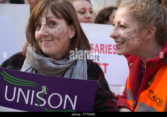 London, UK. 2nd December, 2015. Protesting nurses with the hashtag #paynotpoverty written on their faces protest - Stock Image
