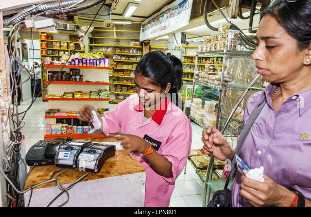 India Asian Mumbai Churchgate Suryodaya grocery store supermarket woman employee credit card scanner using uniform - Stock Image