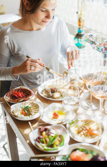 Young woman having meze at table in Lebanese restaurant - Stock-Bilder