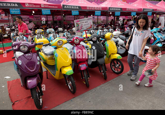 Electric mopeds or scooters for sale at a trade fair in a Chinese city. - Stock-Bilder