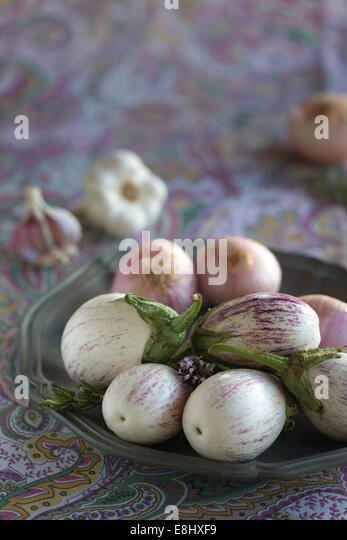 plated white aubergines with purple fine stripes, onion and garlic against purple floral tablecloth - Stock Image