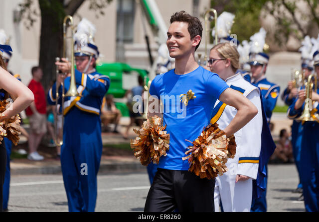 Young Caucasian male high school cheerleader in parade - USA - Stock Image