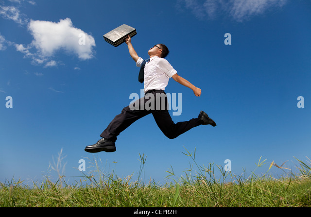 happy businessman running over the grass field - Stock Image