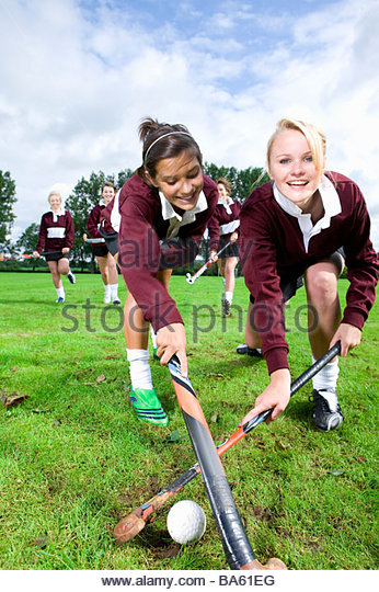 Portrait of smiling teenage girls playing field hockey - Stock Image
