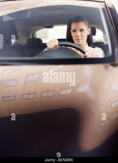 woman driving car. Reflections of building on hood. Copy space - Stock Image